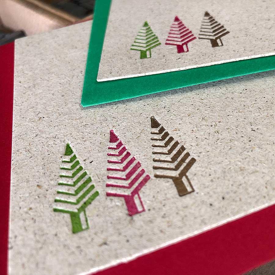 Detalle de tarjeta de felicitación de navidad de tres arbolitos impresos en tres colores sobre papel de hierbas