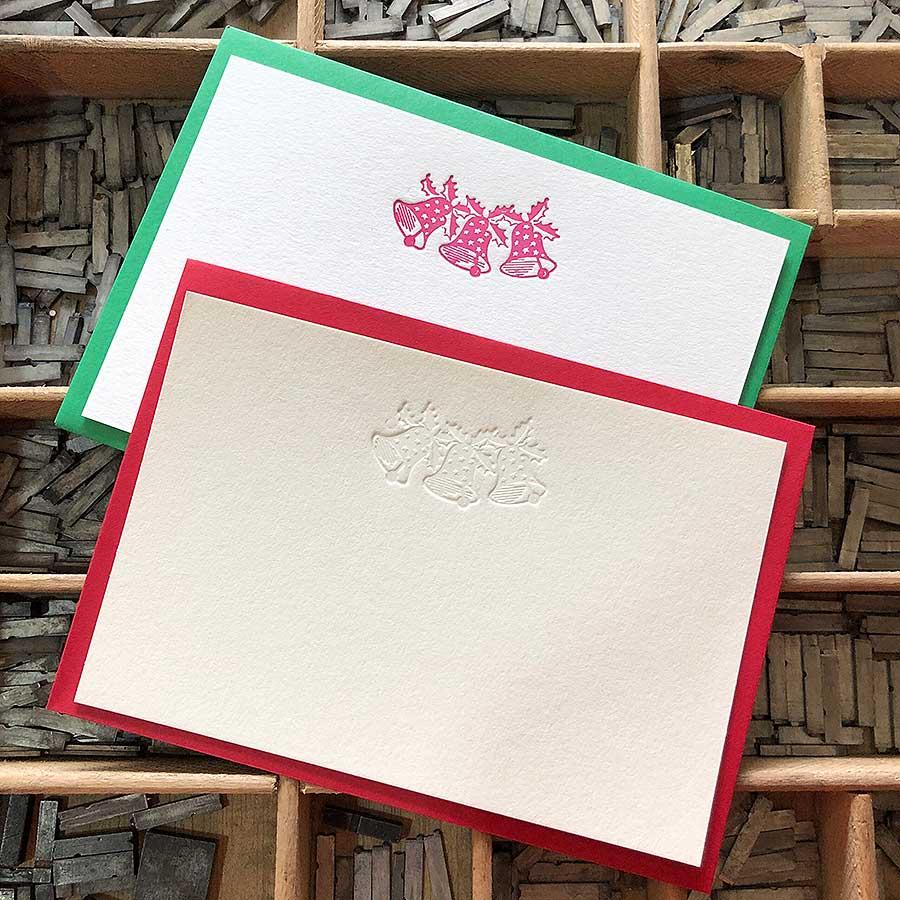 Detalle de tarjetas de felicitación navideña de campanas impresas en tinta roja y golpe seco con sobres de color rojo y verde