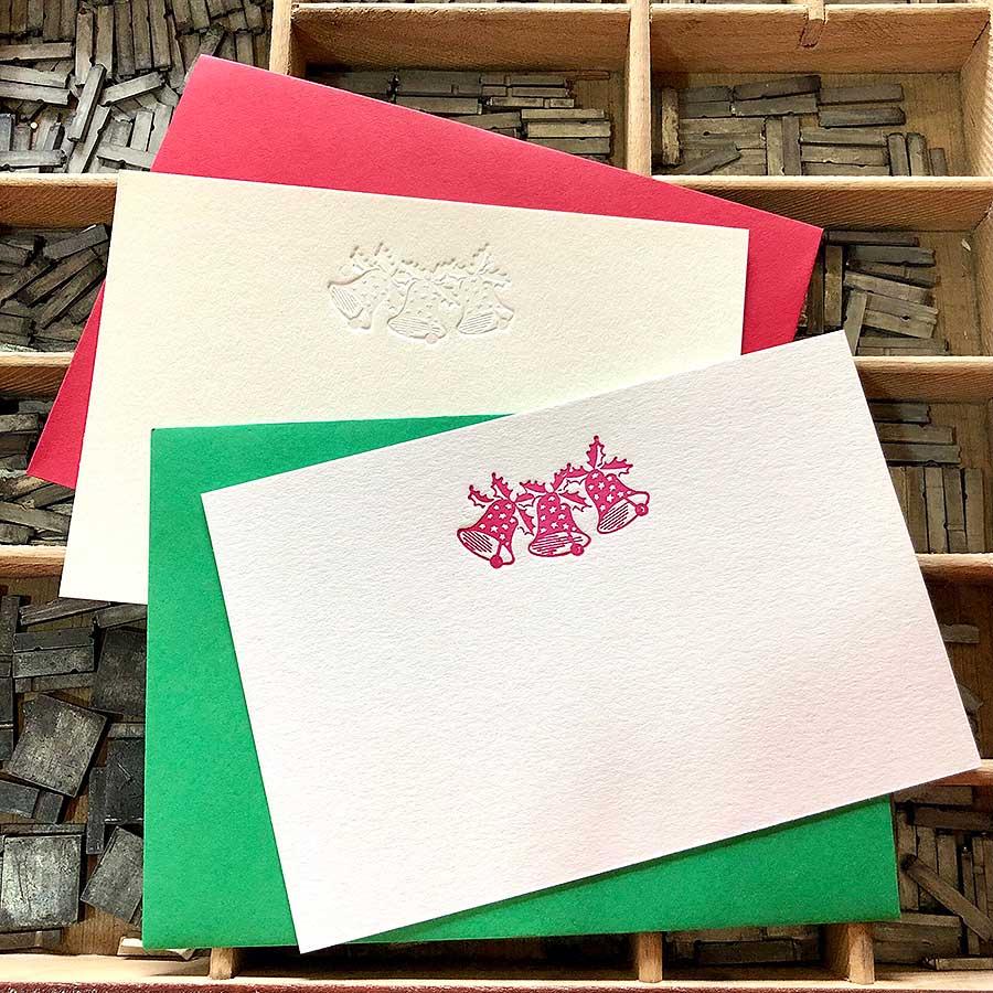 Detalle de tarjetas de felicitación navideña de tres campanas en diferentes colores